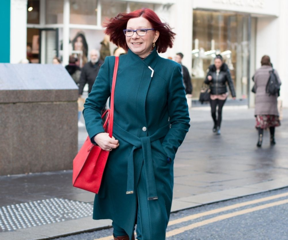 Lucienne walking on high street wearing teal green coat with red bag